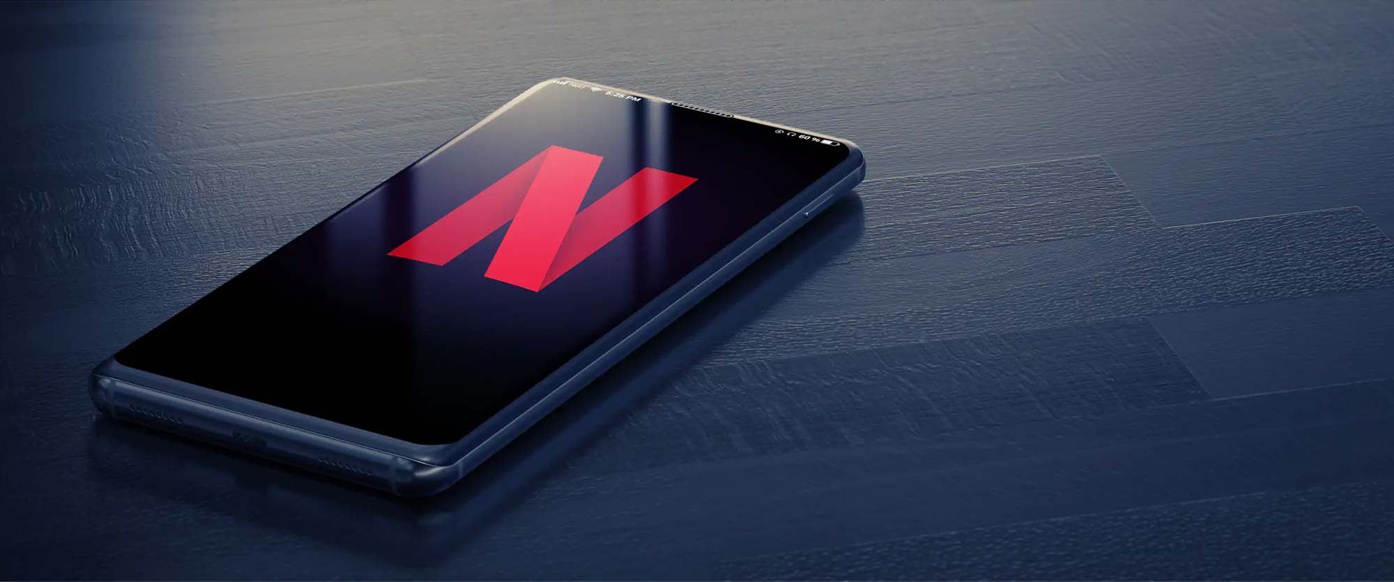 Netflix red logo on iPhone X resting on dark-blue wooden surface