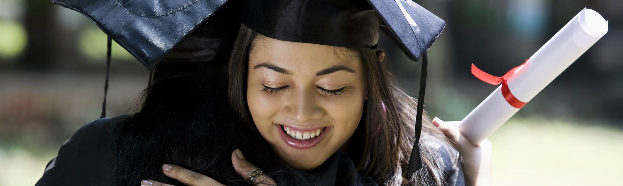 young woman hugging on graduation today, with graduation uniform and certificate in her hand